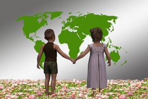 boy and girl holding hands in front of map of world