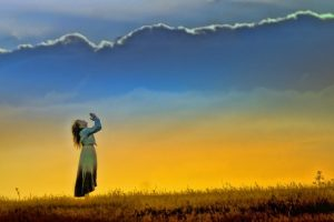 Woman praying surrounded by morning light and clouds