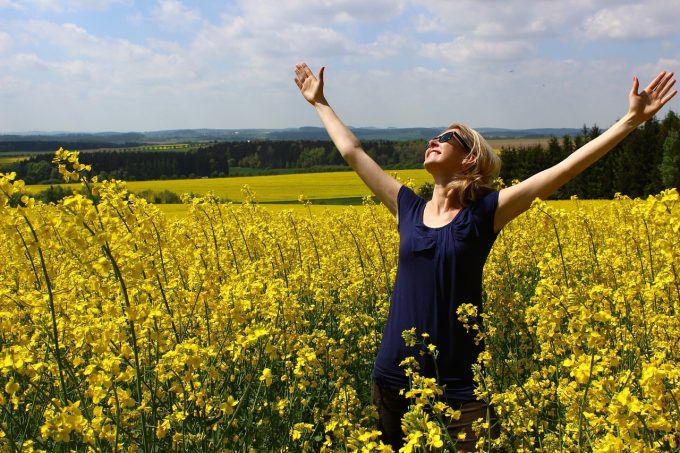 woman in field of flowers with arms outspread