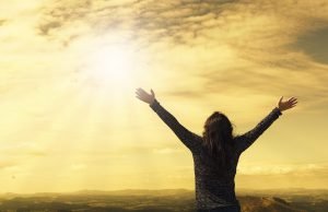 person raising arms in praise