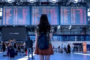 woman in airport looking at flight schedule