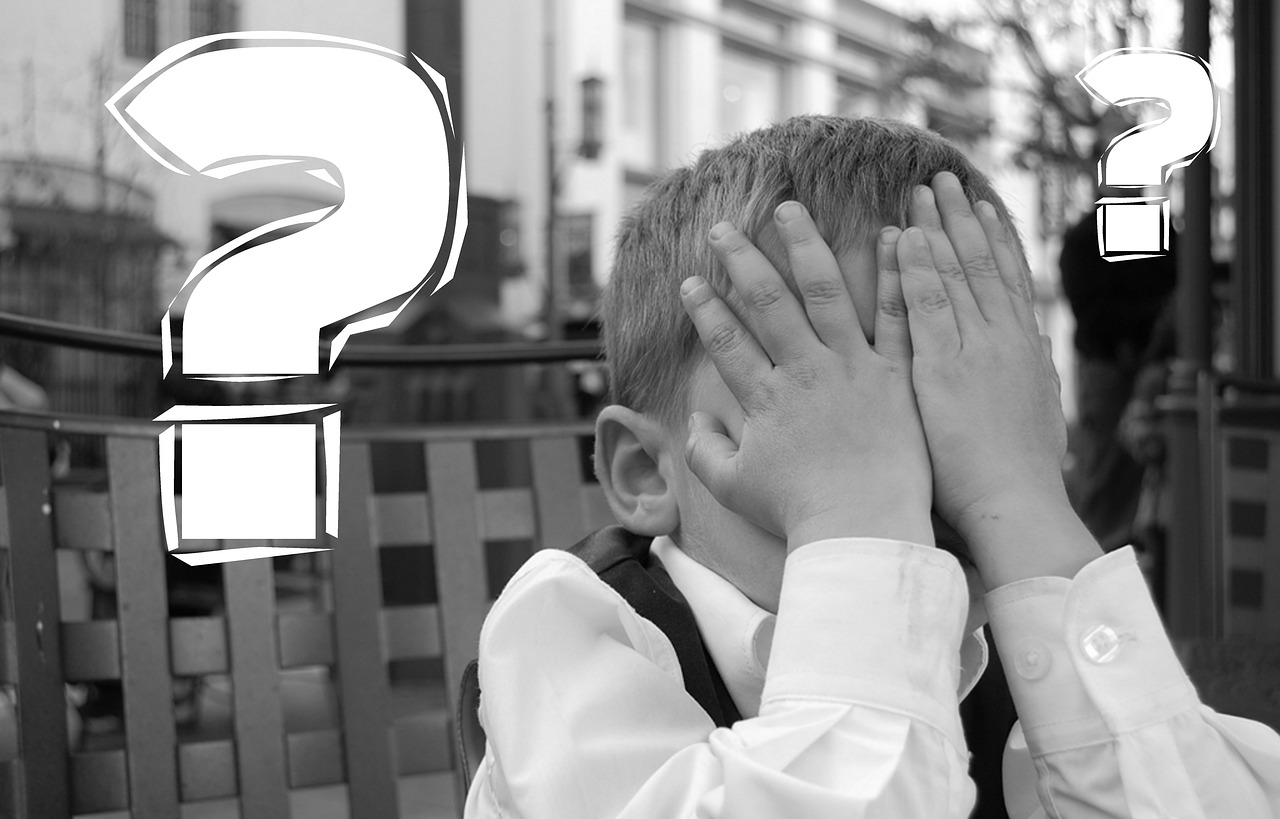 small boy covering face with hands next to question mark