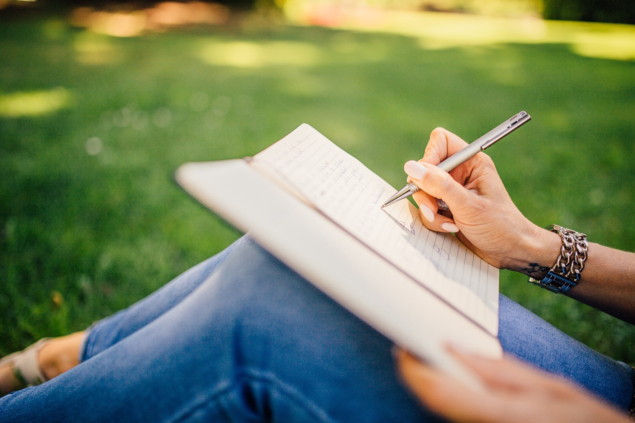 person sitting outside writing in notebook