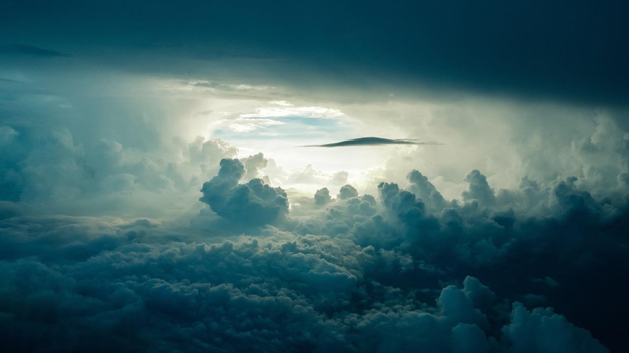 sun shining through clouds in the sky