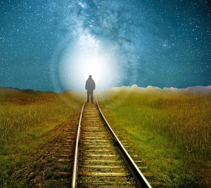 person at end of railroad tracks walking into light