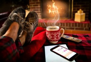 feet in slippers before a roaring fire with a cup of coffee