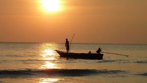 two people fishing on a boat as sun rises